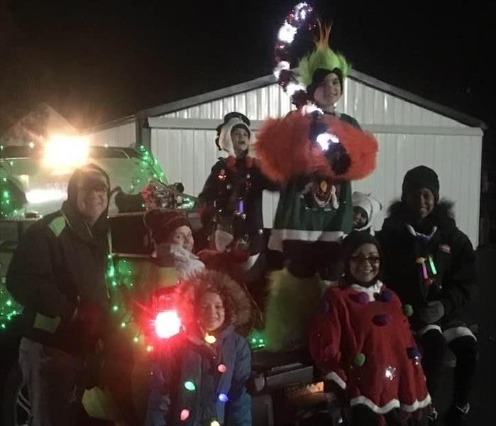 Several SERVPRO employees and children dressed in Christmas sweaters on the bed of a SERVPRO truck decorated with lights