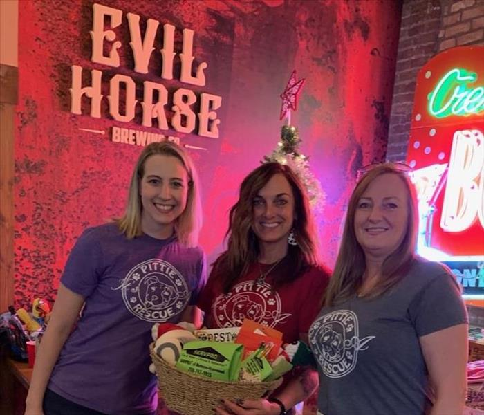 Three female staff members from It's a Pittie Rescue holding a gift basket donated by SERVPRO