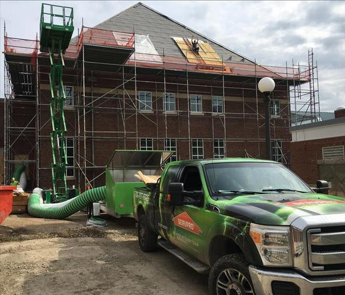 scaffolding jobsite with SERVPRO truck, worker on roof