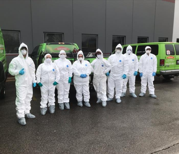 A group of cleaning technicians wearing PPE in front of a commercial building