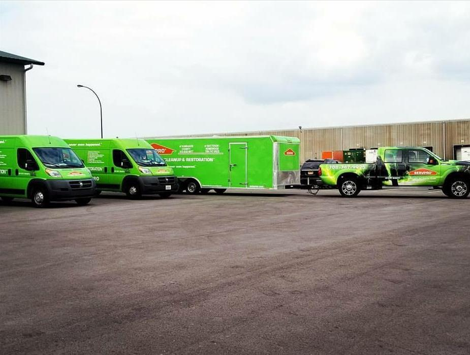 Three bright green trucks pulling away from a warehouse headed to a cleaning project