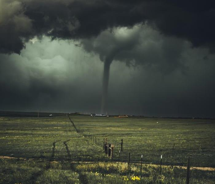 Tornado in the sky over field