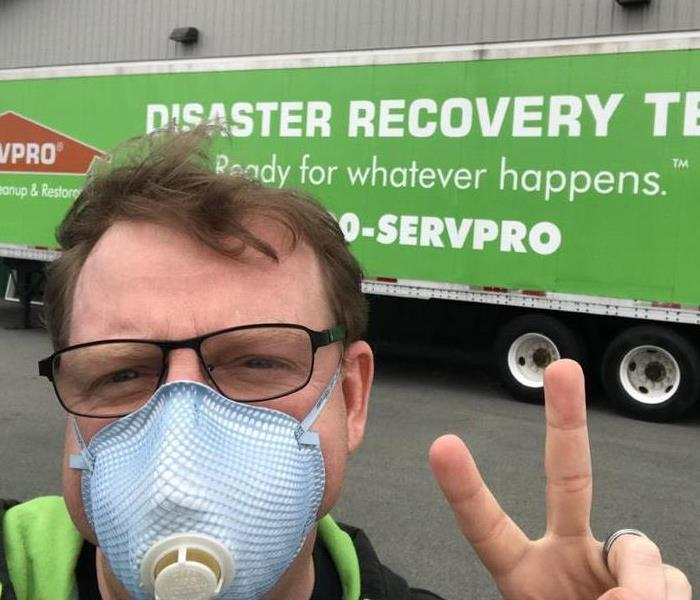 man in a mask in front of a large green semi trailer