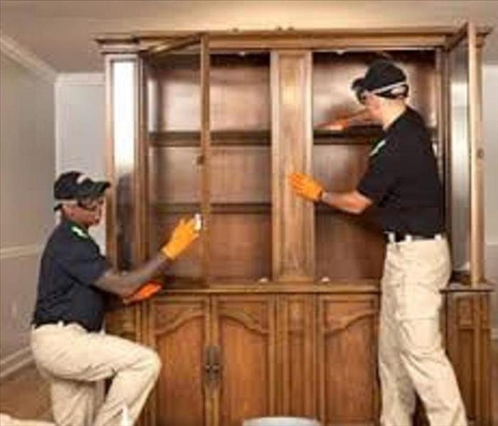 SERVPRO technicians cleaning fire damages cabinet